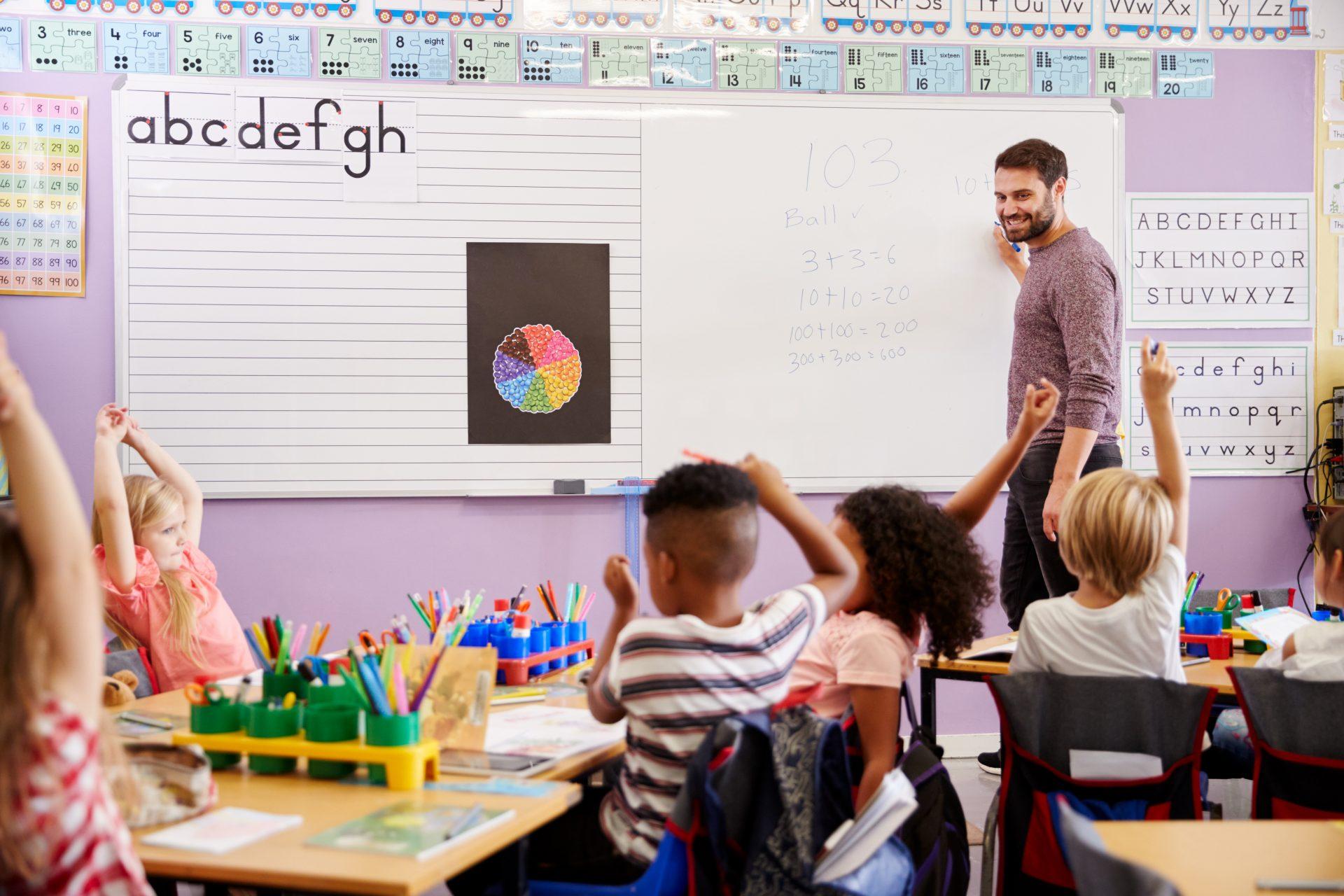 Barn rekker opp hånden i klasserom