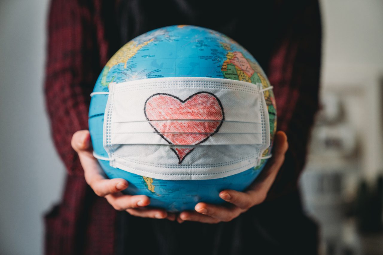 Dame som holder en globus med et munnbind med et hjerte tegnet i midten