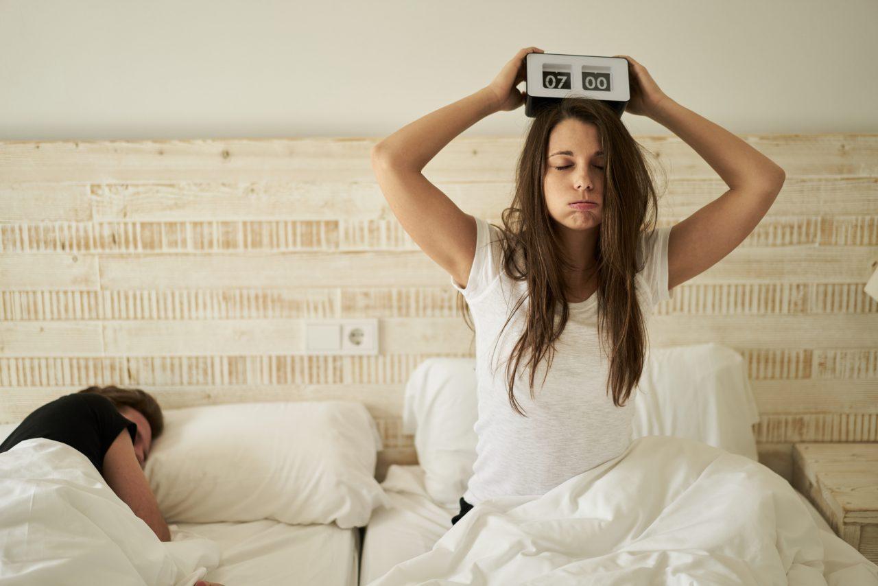Dame som sitter oppgitt i sengen med en vekkeklokke over hodet