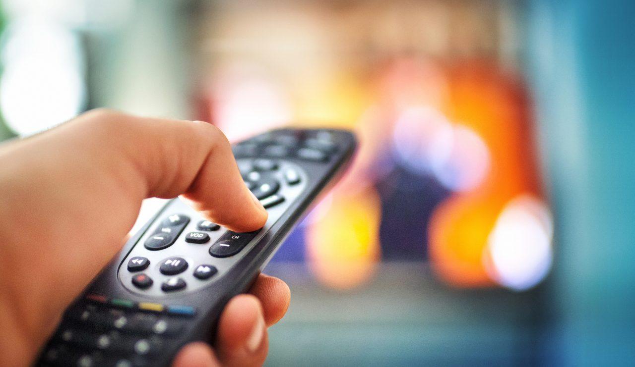 En hånd som holder en fjernkontroll til et TV