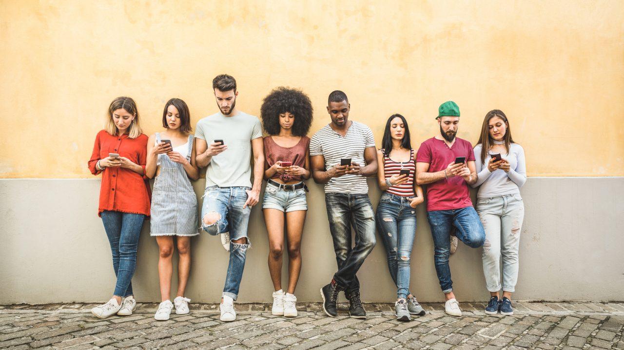 Alle i en vennegjeng står ute mot en vegg og ser på hver sin smarttelefon