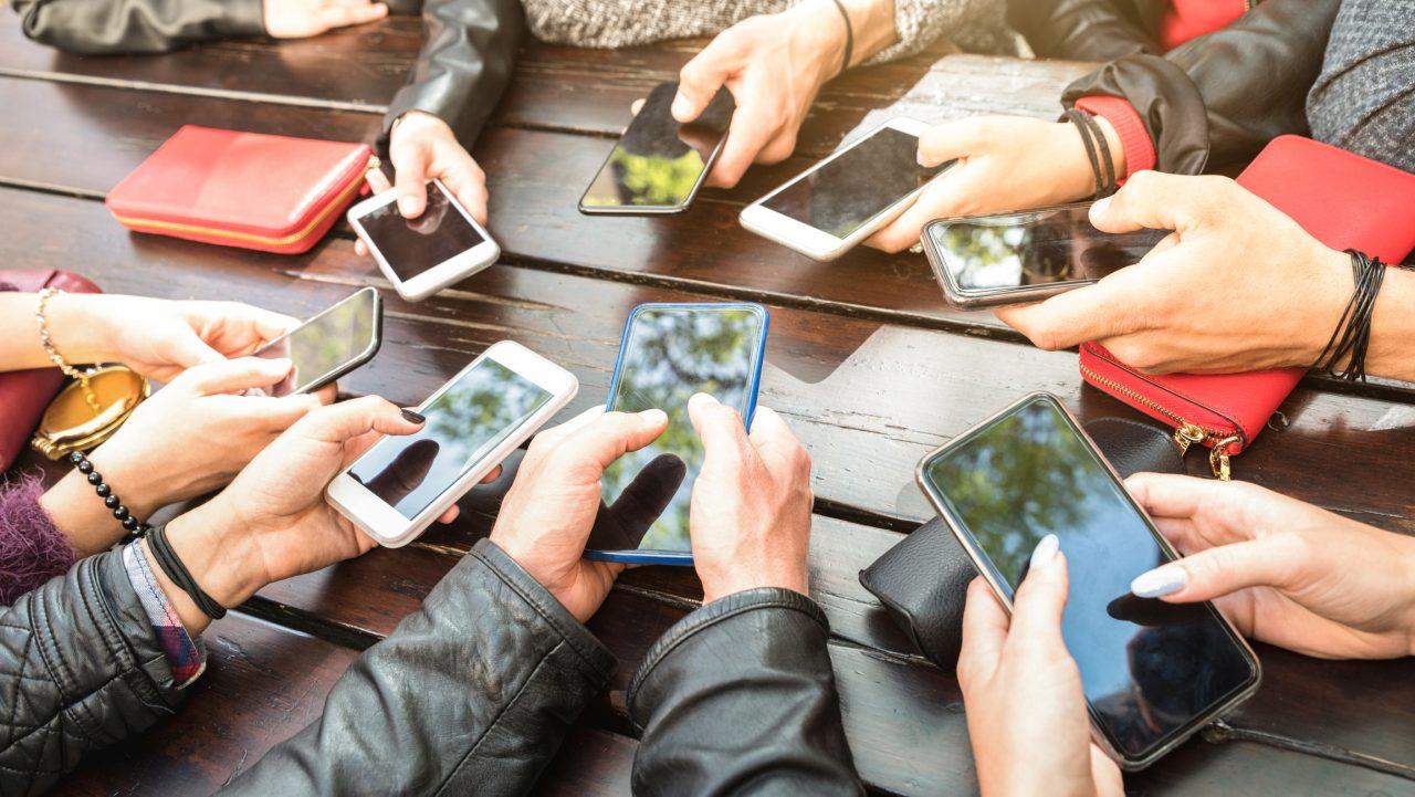 En gruppe med tenåring som alle holder en smarttelefon