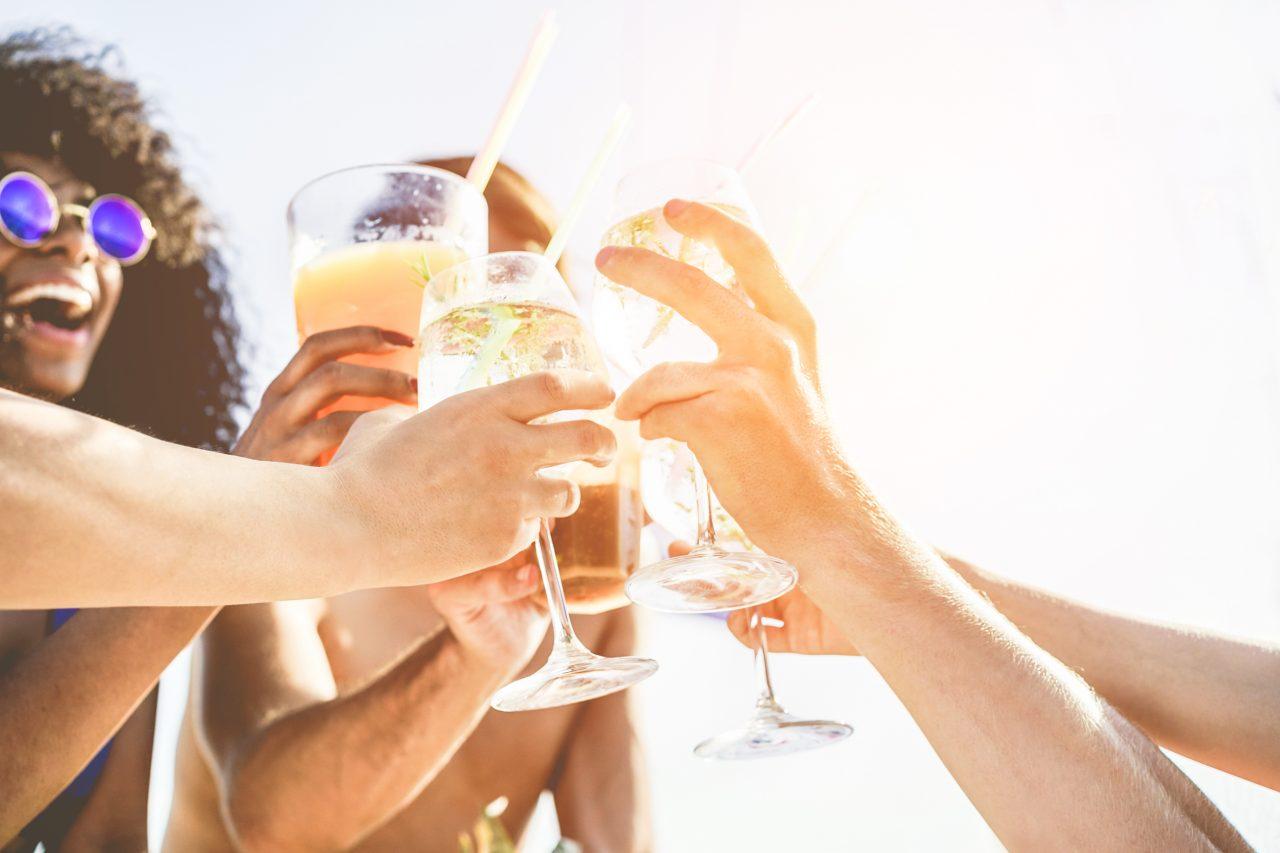 Vennegjeng som skåler med hver sin drink utendørs