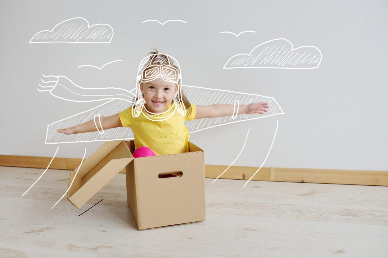 Liten jente leker pilot i en pappeske