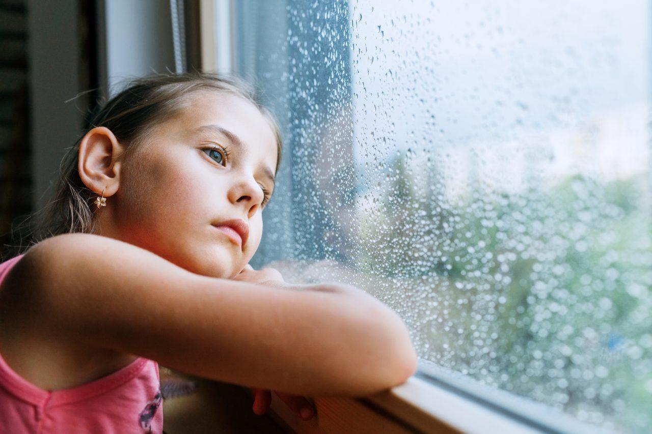 Liten jente ser tenkende ut av vinduet med regndråper på