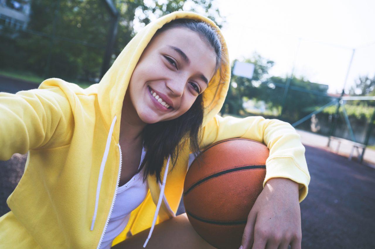 Tenåringsjente som spiller basketball