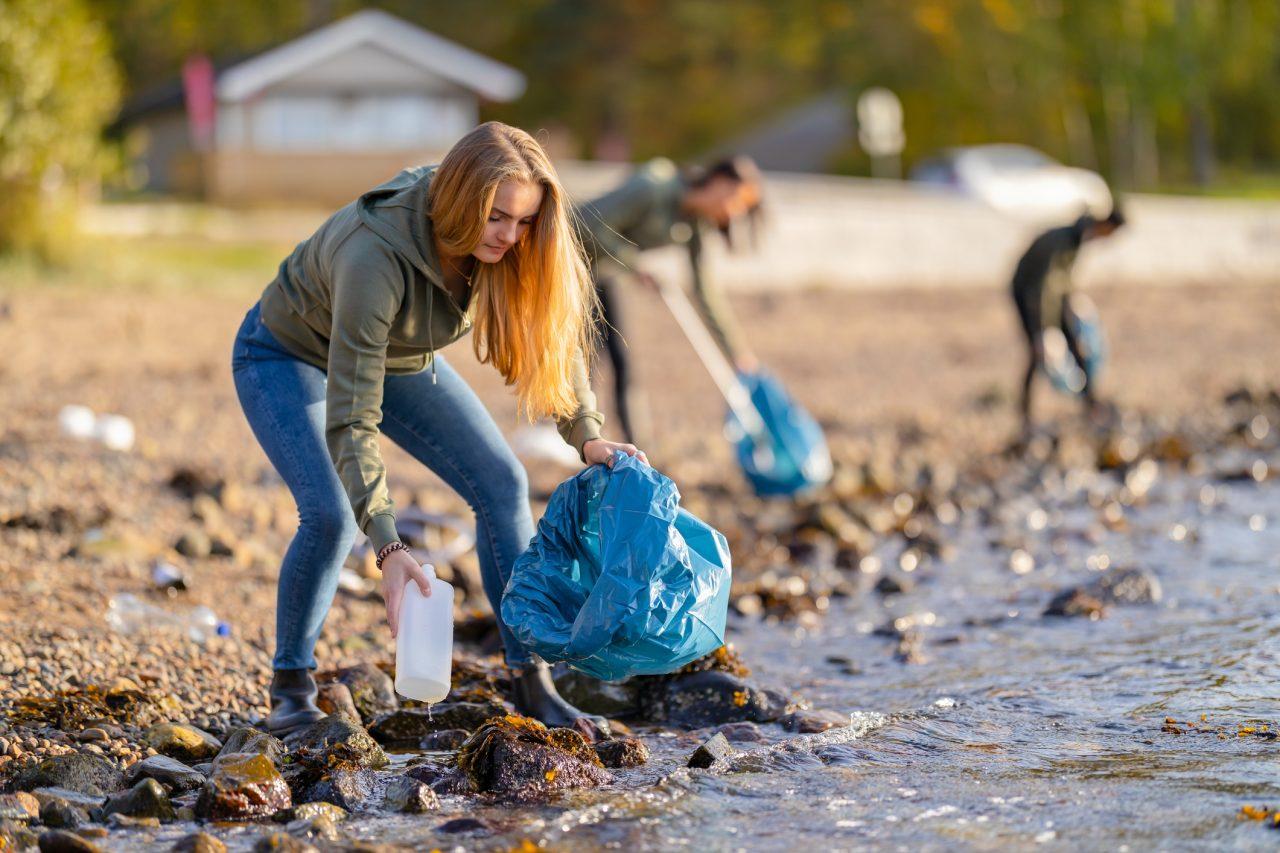 Ungdommer plukker søppel på en strand