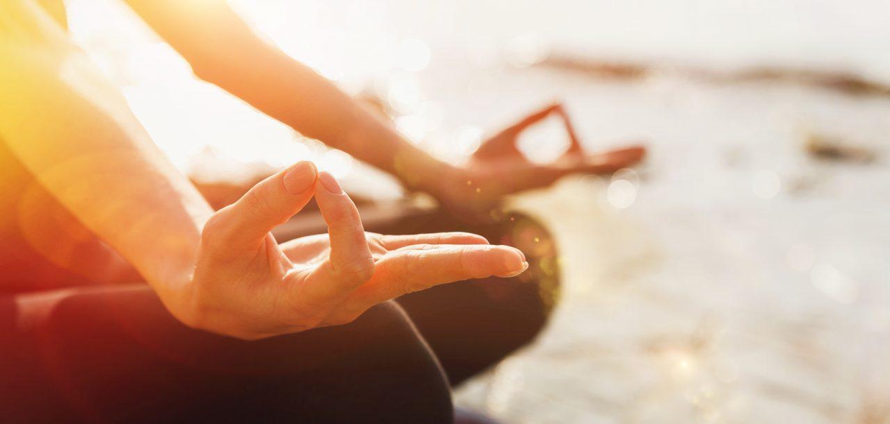 Dame praktiserer yoga i lotus posisjon utendørs