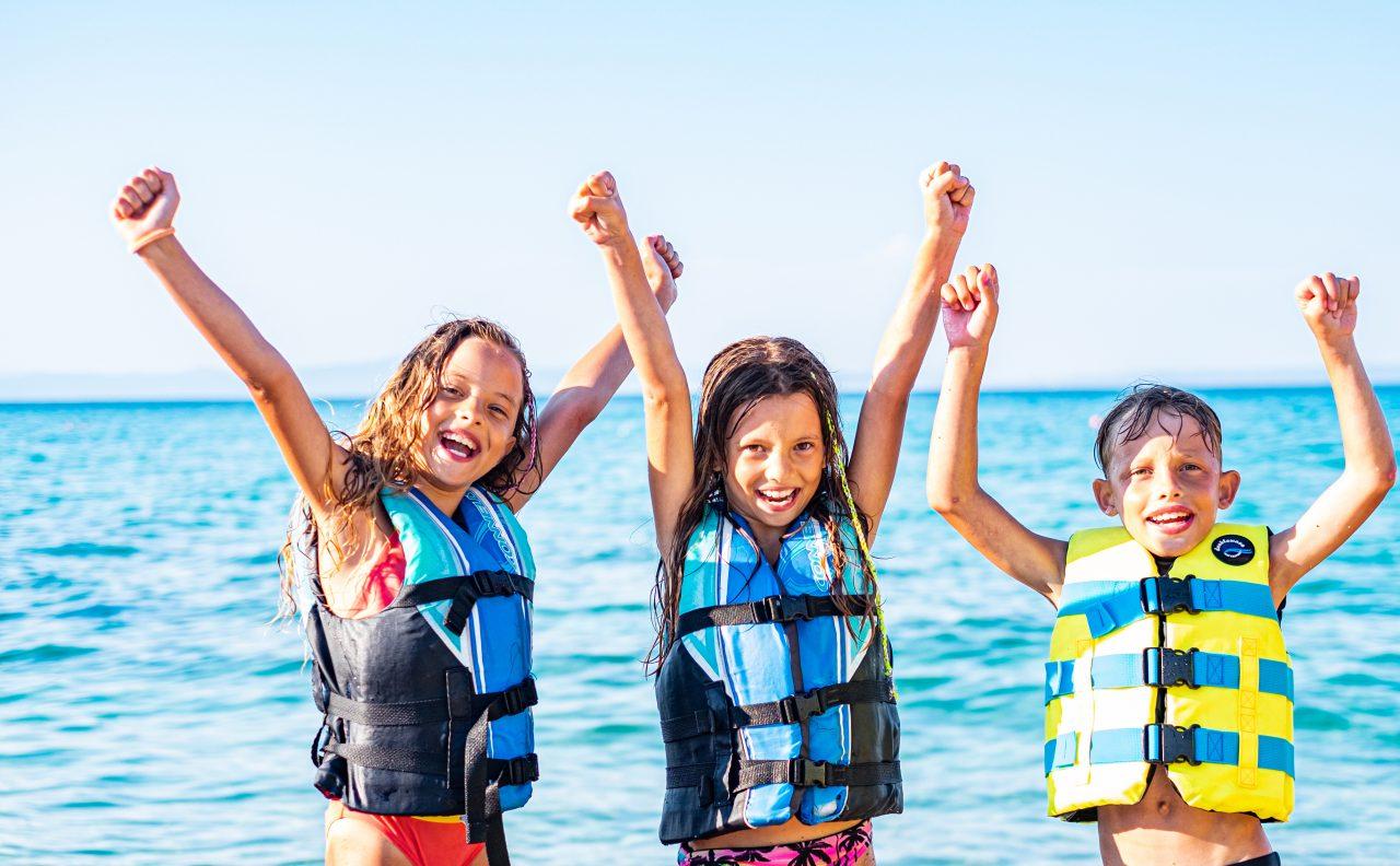 Tre glade barn med redningsvester