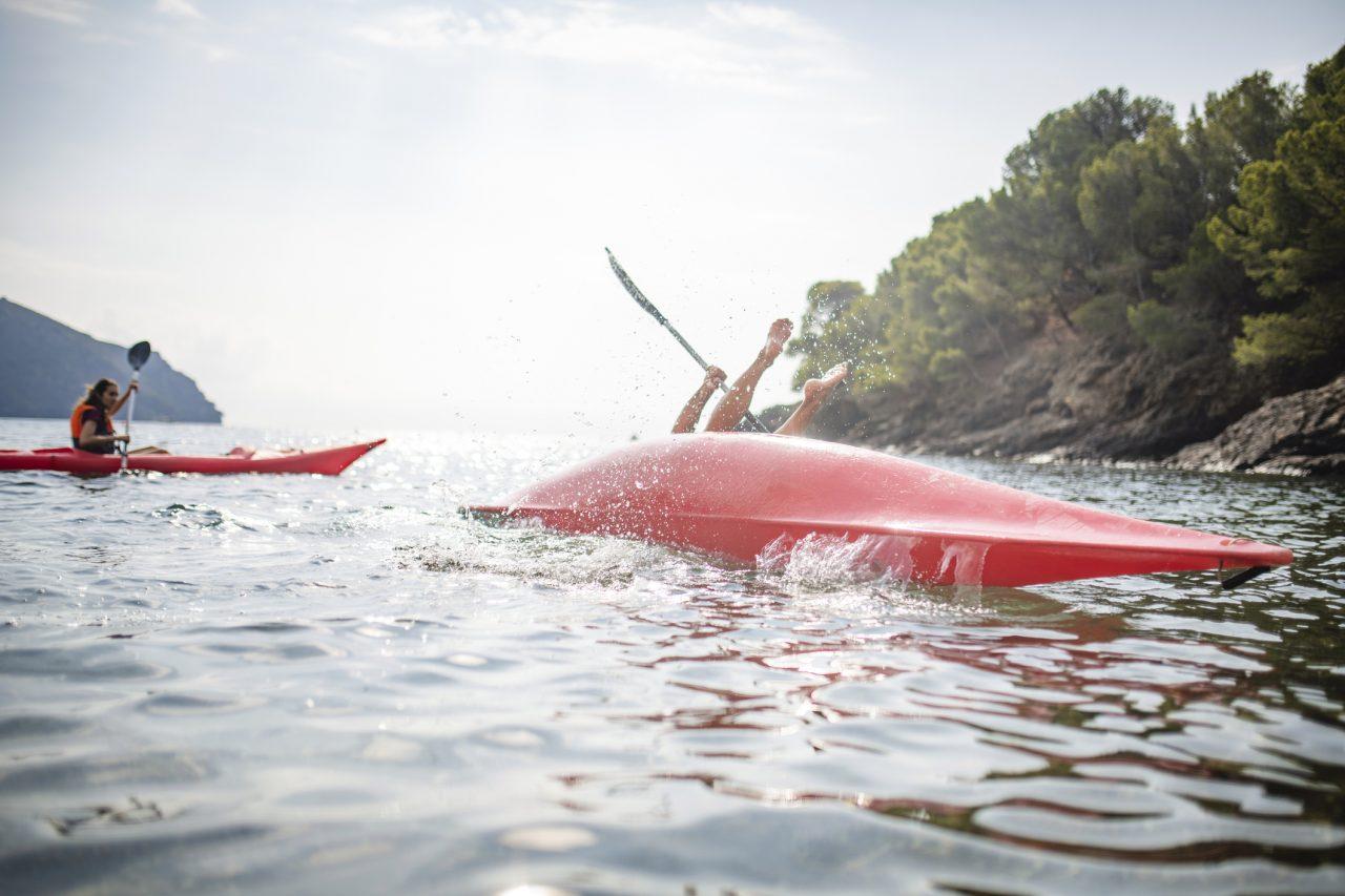 Mann som detter ut i havet fra kajakken sin mens en person i bakgrunnen padler sin egen kajakk