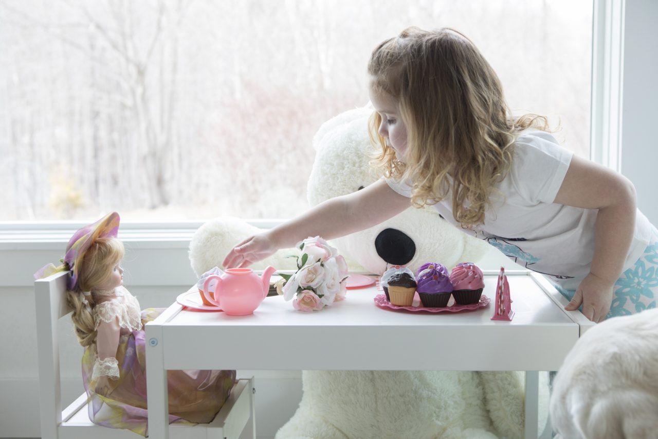 Et barn som har te selskap med lekene hennes