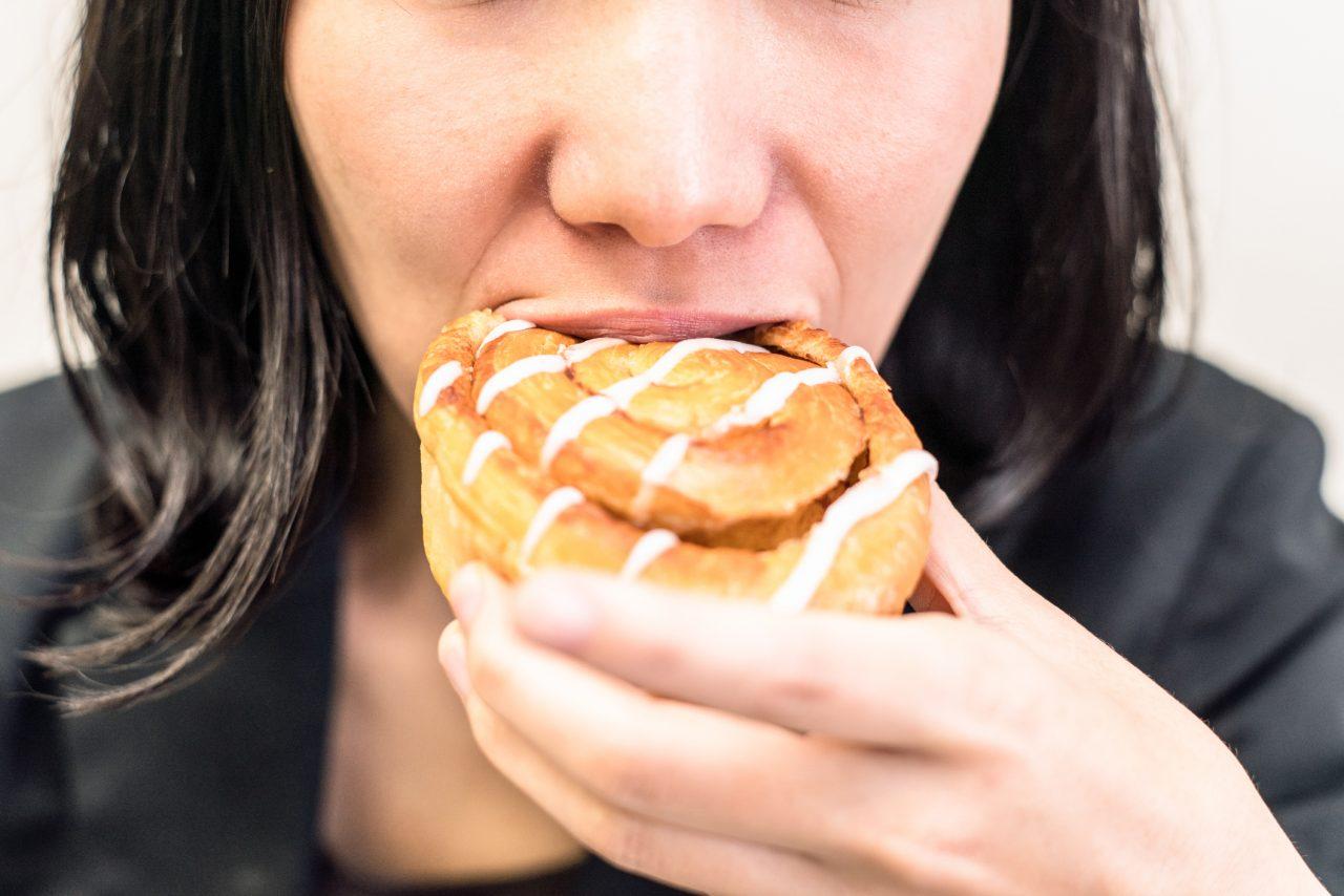 Forretningskvinne spiser en kanelsnurr