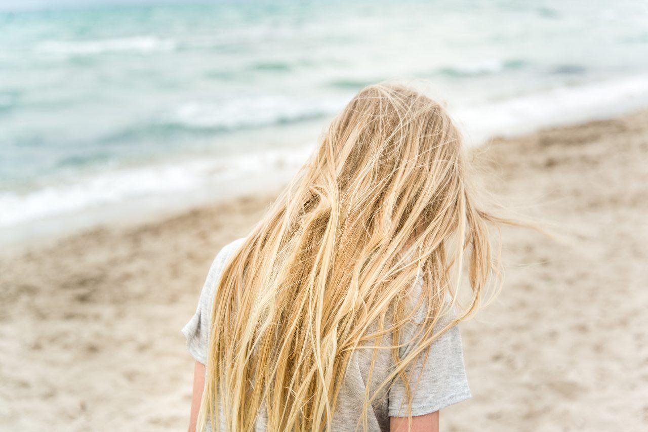Ung jente med blondt hår på en strand