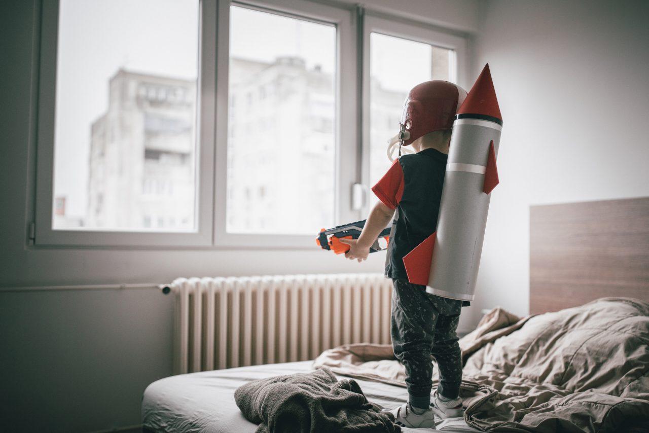 Ung gutt stående på senga med romrakett og leke pistol