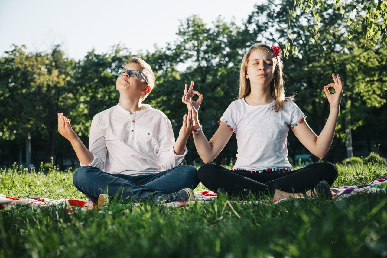 Jente og gutt som mediterer i en park