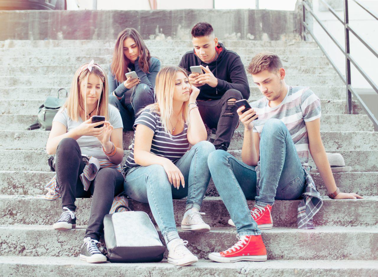 Jente uten smarttelefon mens alle andre i gjengen rundt henne sitter opphengt i hver sin smarttelefon