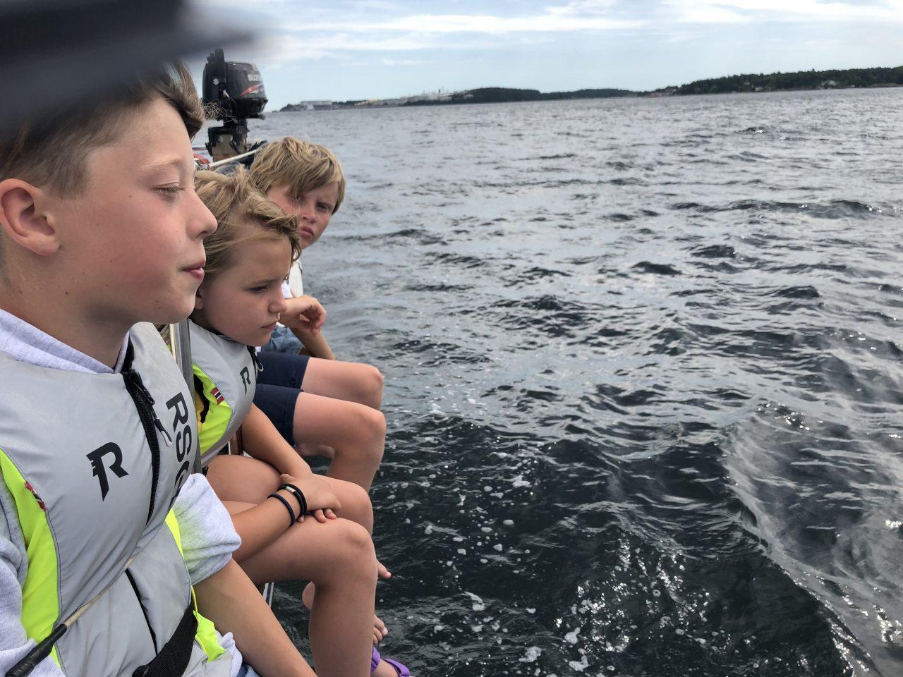 Gutter sitter på kanten av en båt