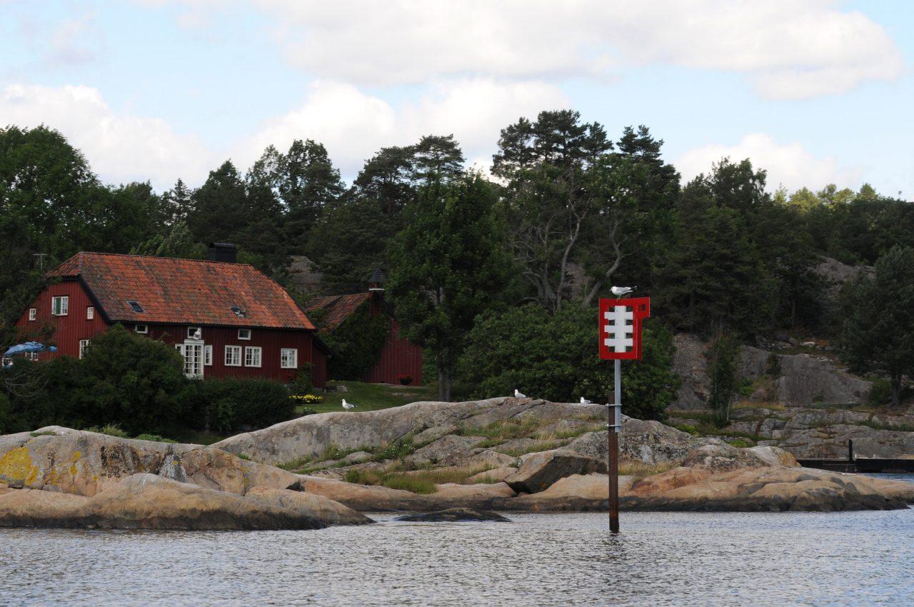 Sjømerke med hytte i bakgrunnen