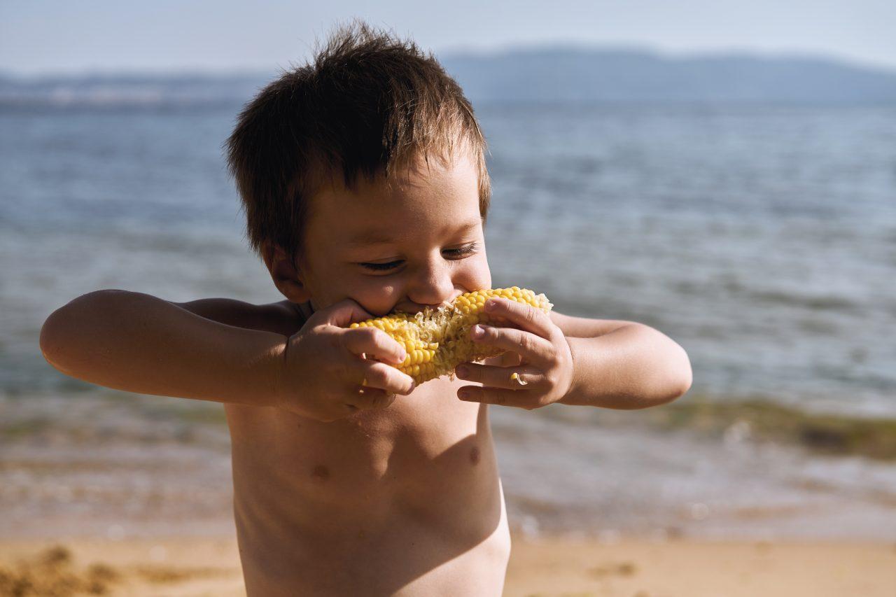 Gutt spiser maiskolbe på stranden