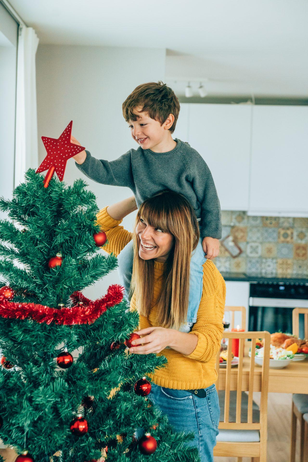 Mor med sønn på skuldrene som setter julestjerne på toppen av et juletre