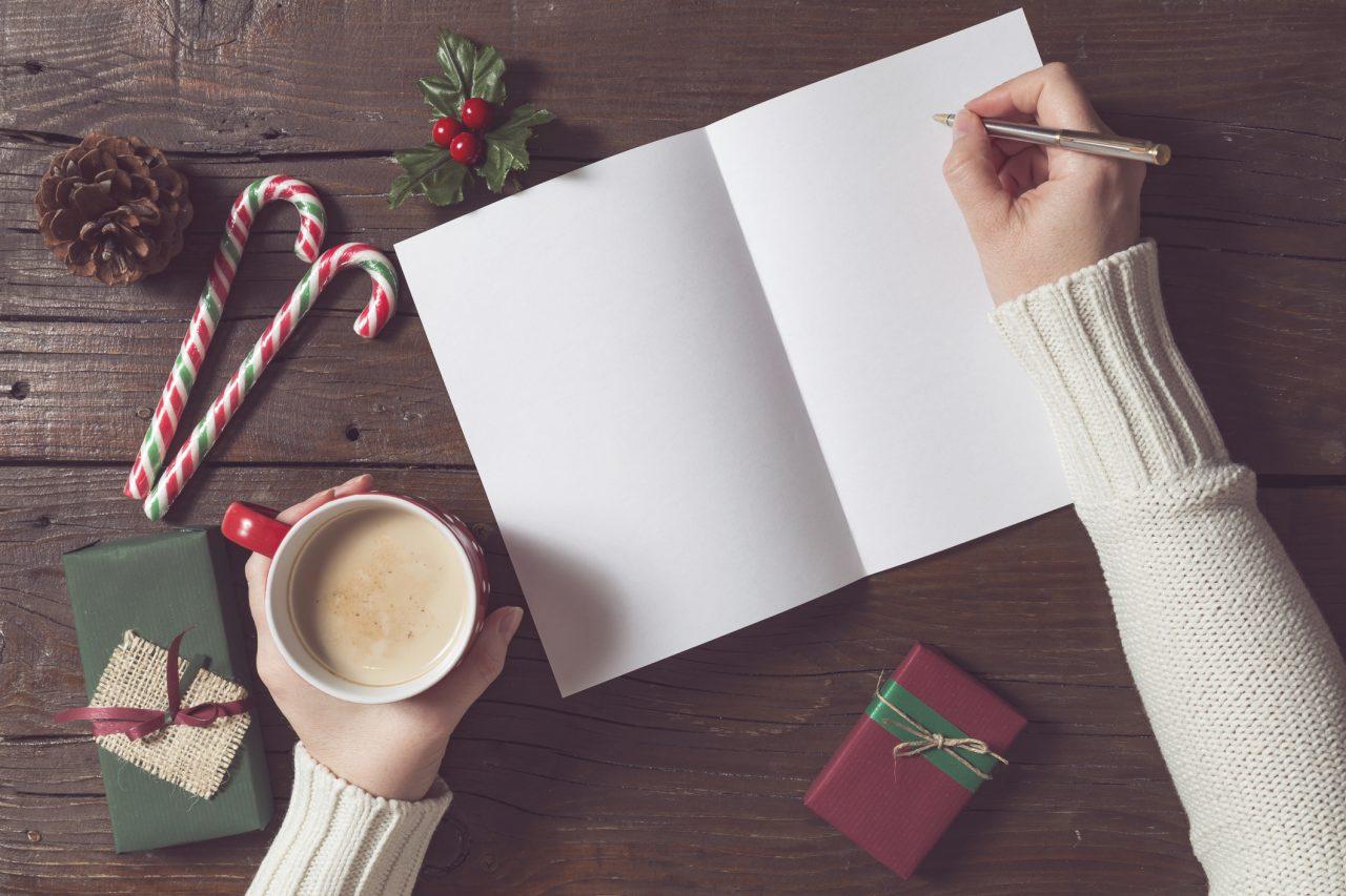 Dame som skriver et brev til julenissen med juledekorasjoner rundt på bordet