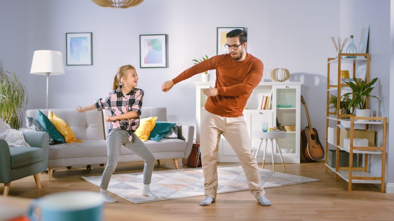 Far og datter danser sammen i stua