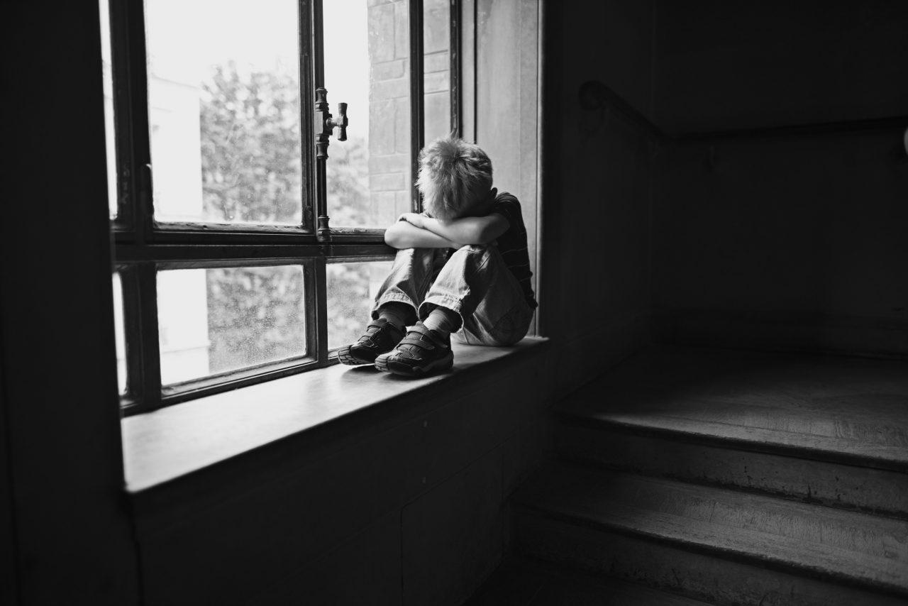 Gutt som sitter i et vindu og er lei seg