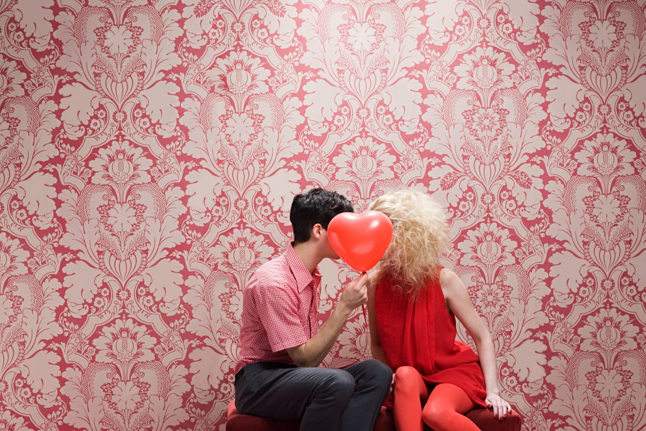 Forelsket par kysser bak hjerteballong