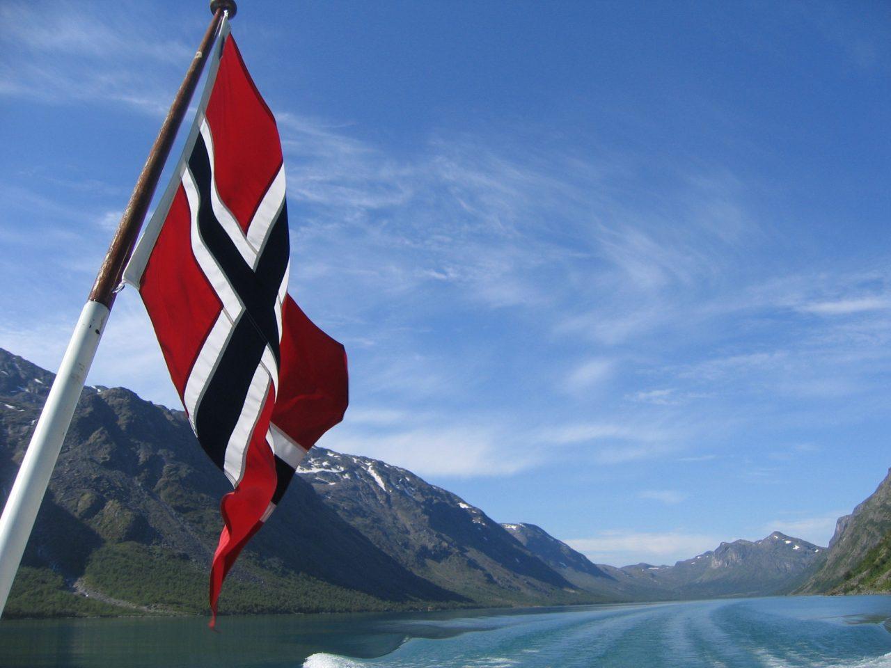 Norske flagget som flagrer bak en båt