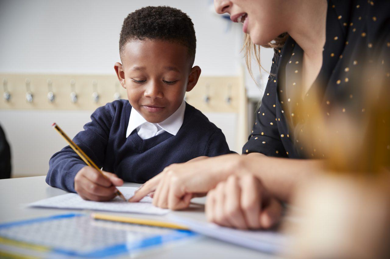 En lærer som hjelper en gutt med skolearbeid