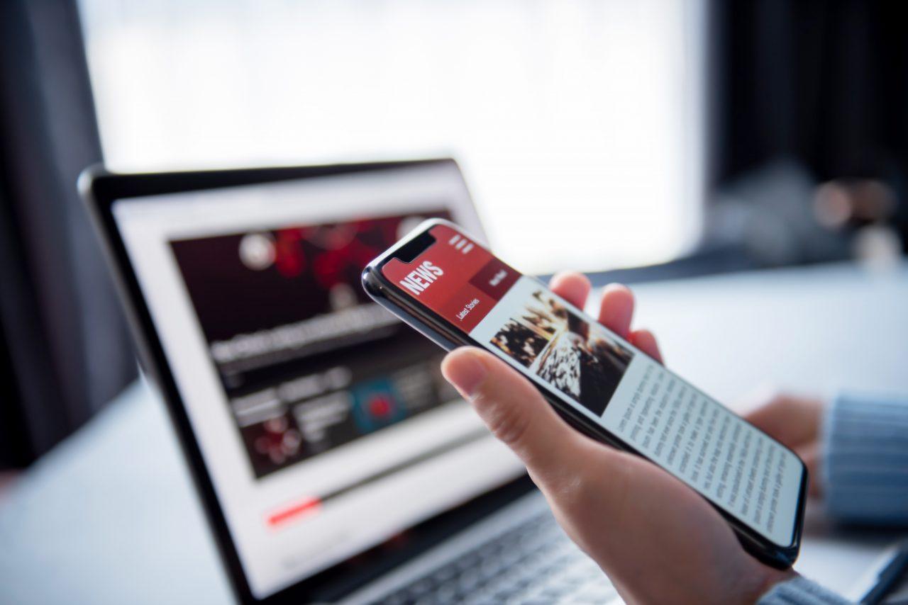 En person som sjekker nyhetssider på mobil og PC
