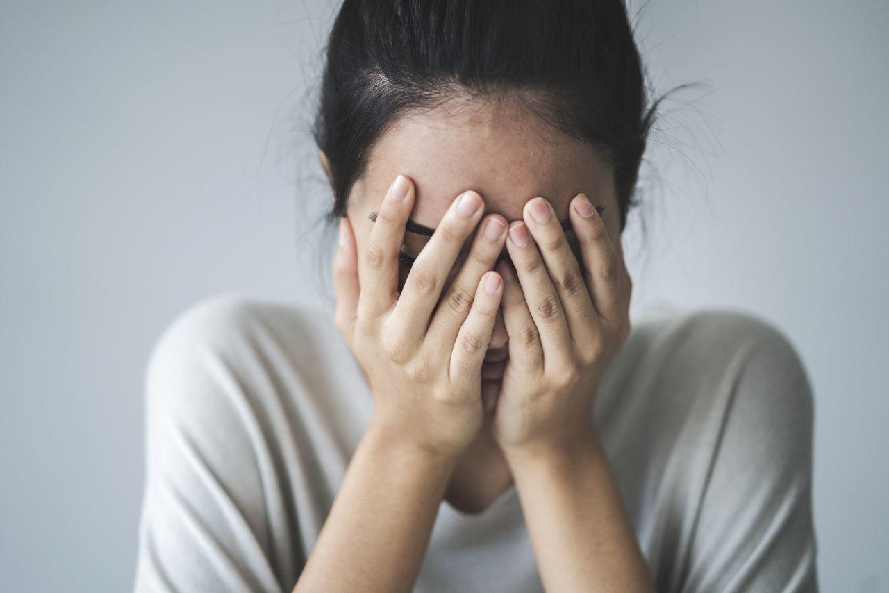 Ung kvinne som gjemmer ansiktet i hendene sine