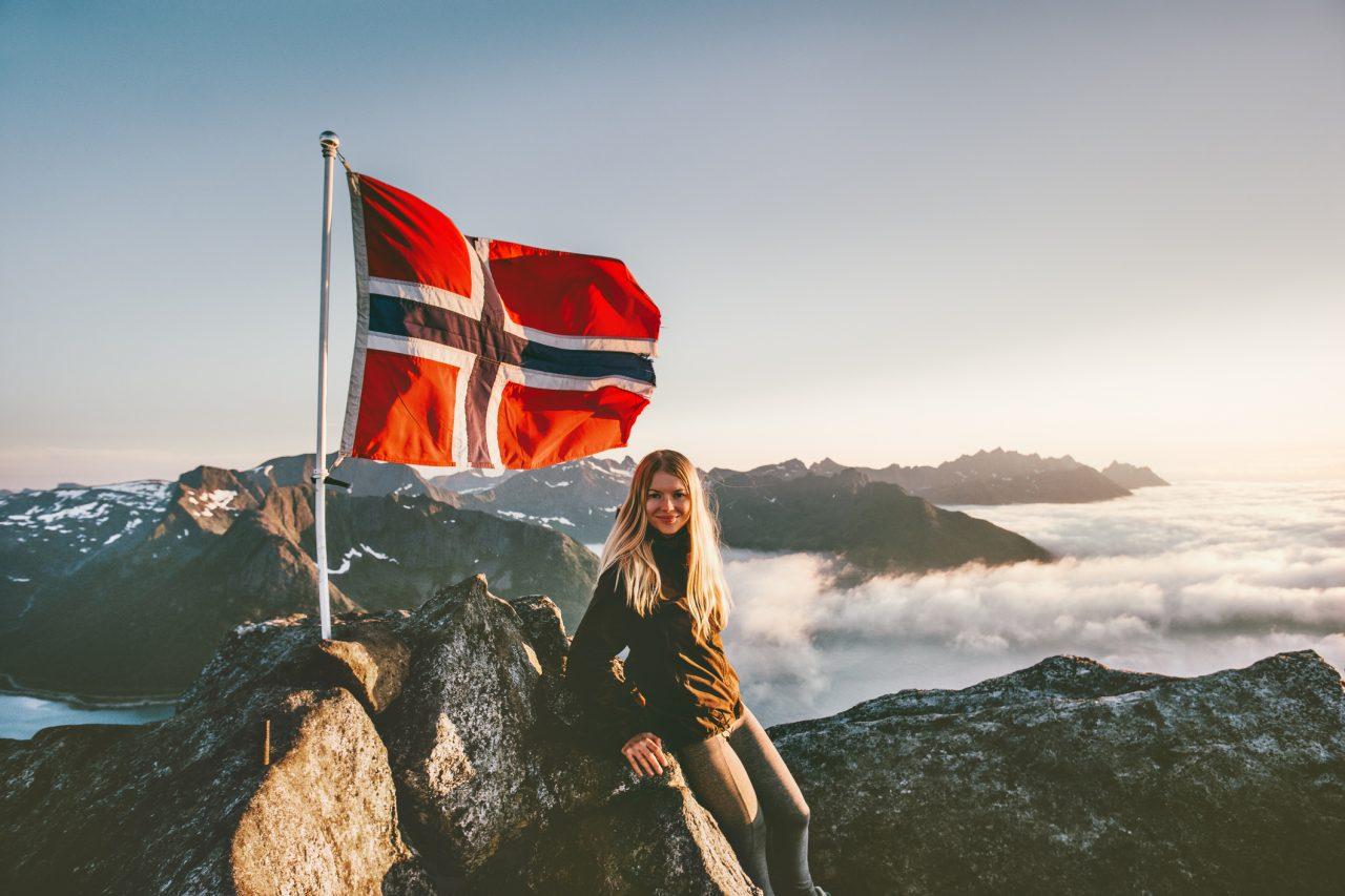 Dame på toppen av et fjell med det norske flagget