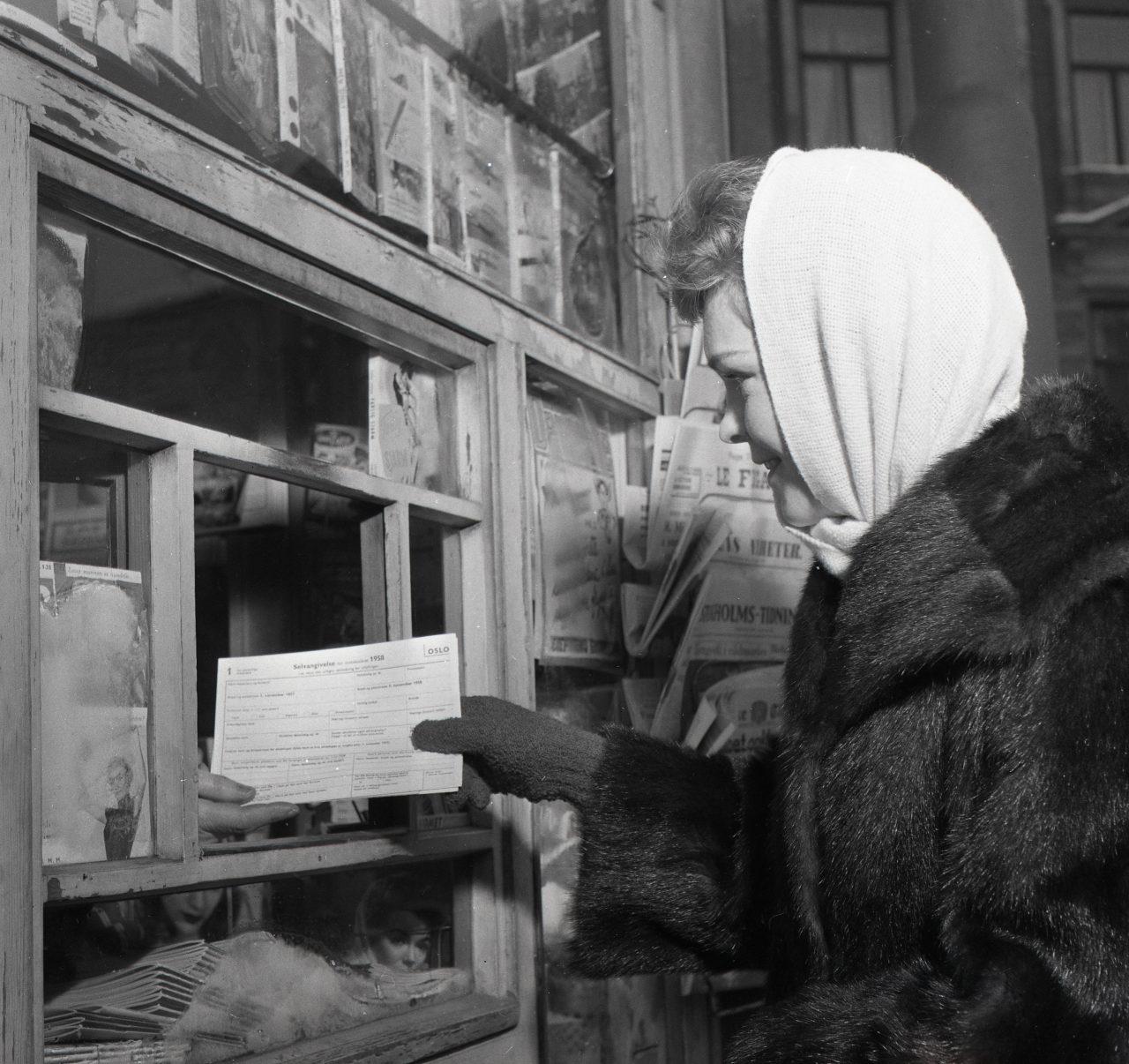 Kvinne som henter selvangivelsesskjema for Oslo 1958 i en kiosk
