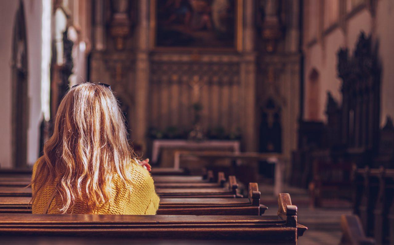 Kvinne ber en bønn i kirken