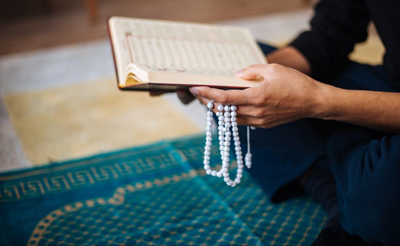 Muslimsk mann holder Koranen og ber en bønn