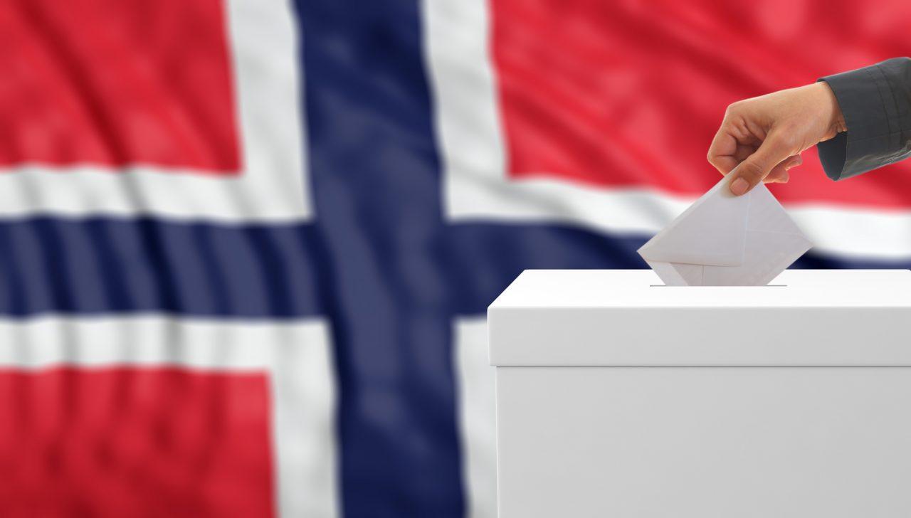 En som stemmer på stortingsvalget med det norske flagget i bakgrunnen