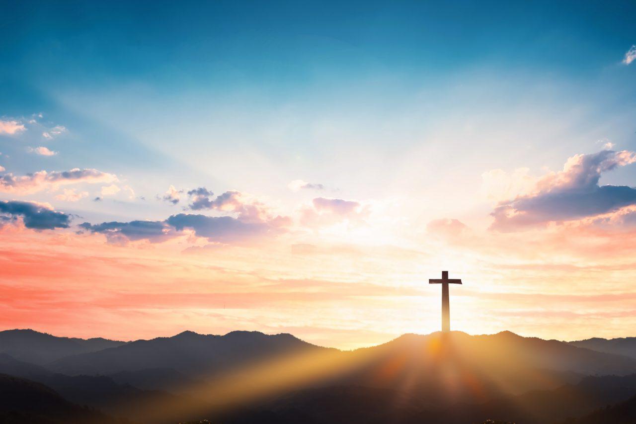 Kors på et fjell i solnedgang