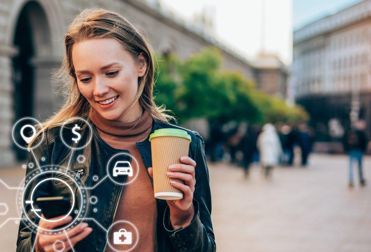 Dame drikker kaffe og ser på mobilen