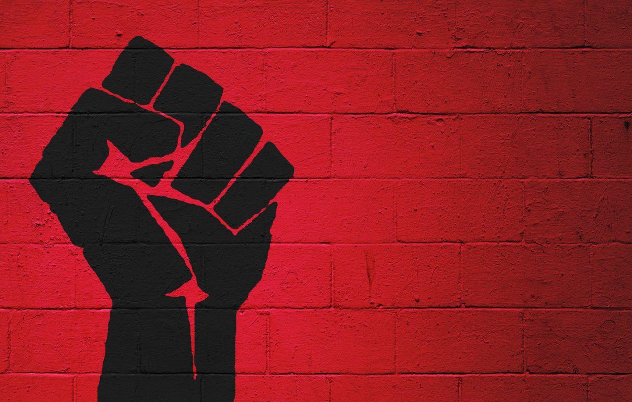 En knyttet neve malt på en rødmalt vegg