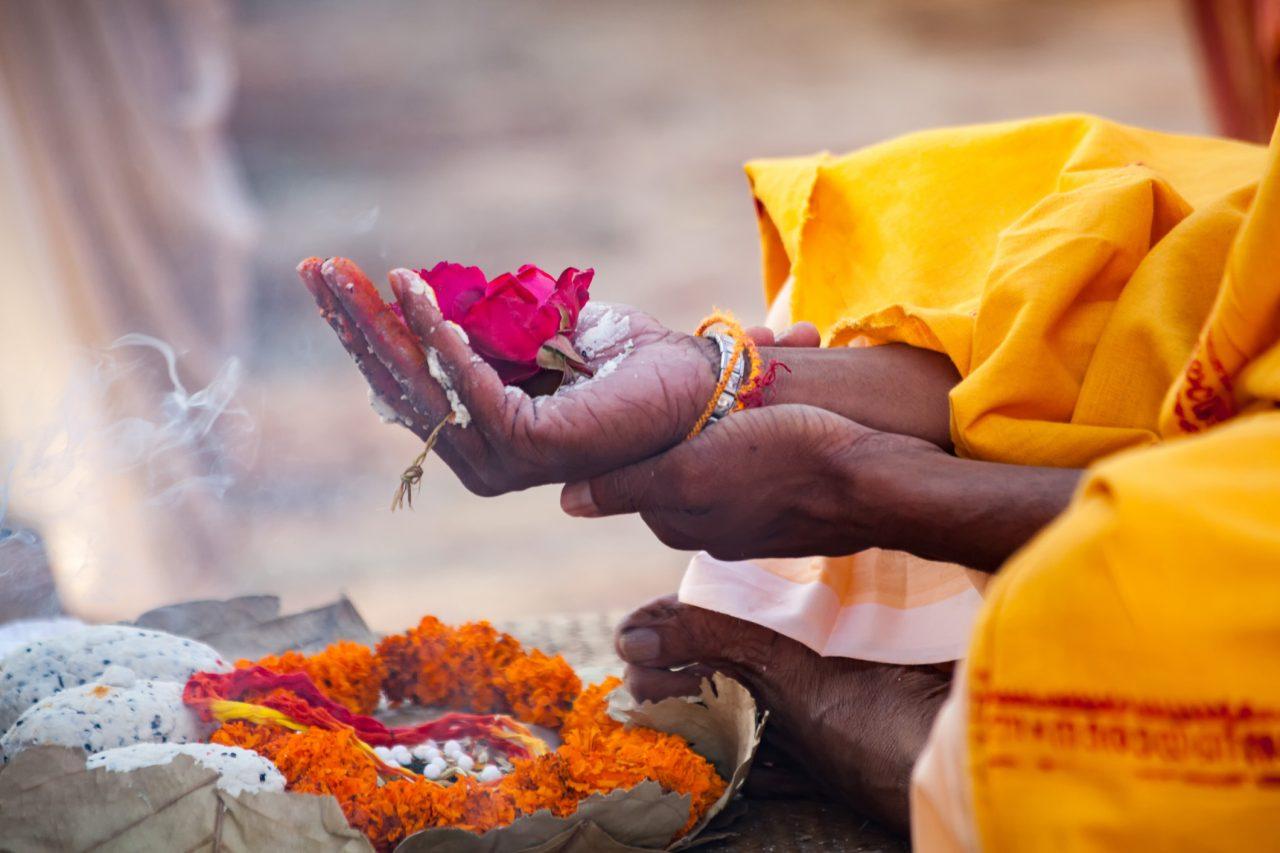 Hellige blomster i en hånd ved elven Ganges
