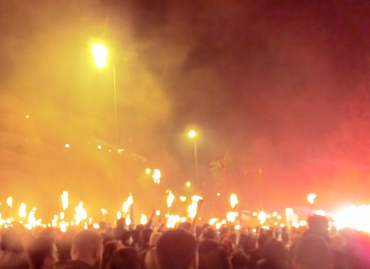 Mennesker som går i demonstrasjonstog på kvelden