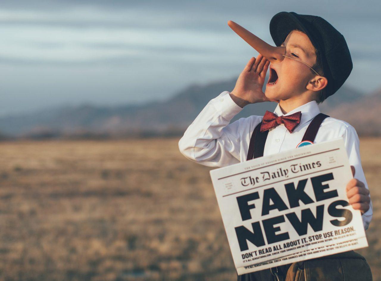 Gutt med avis der det står Fake news
