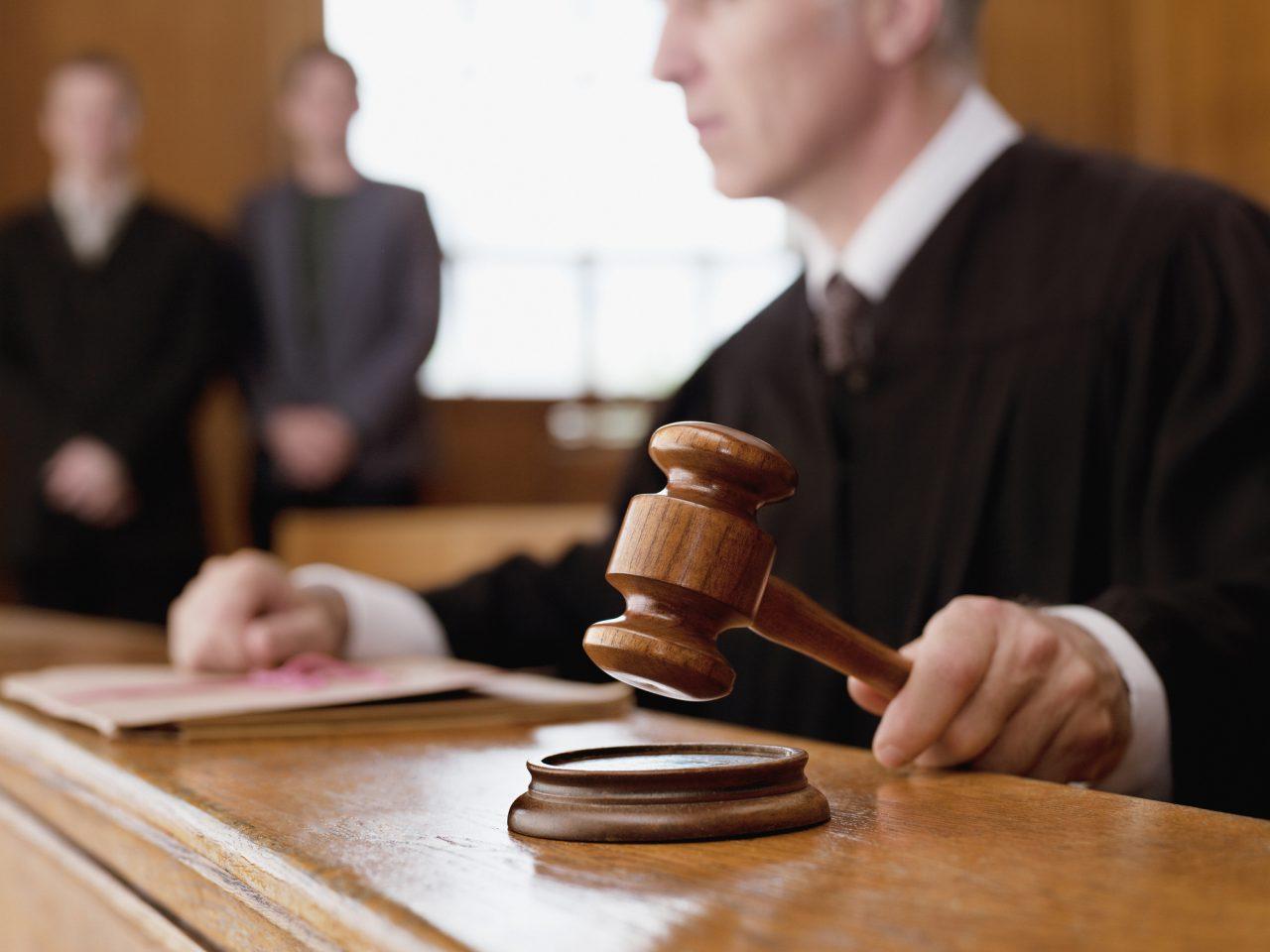 En dommer som holder en klubbe i en rettsal