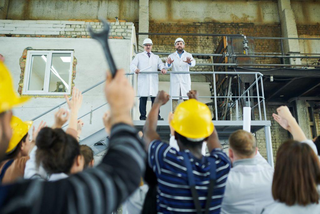 Streikende på en fabrikk ser opp på sjefene som står i en trapp over dem.