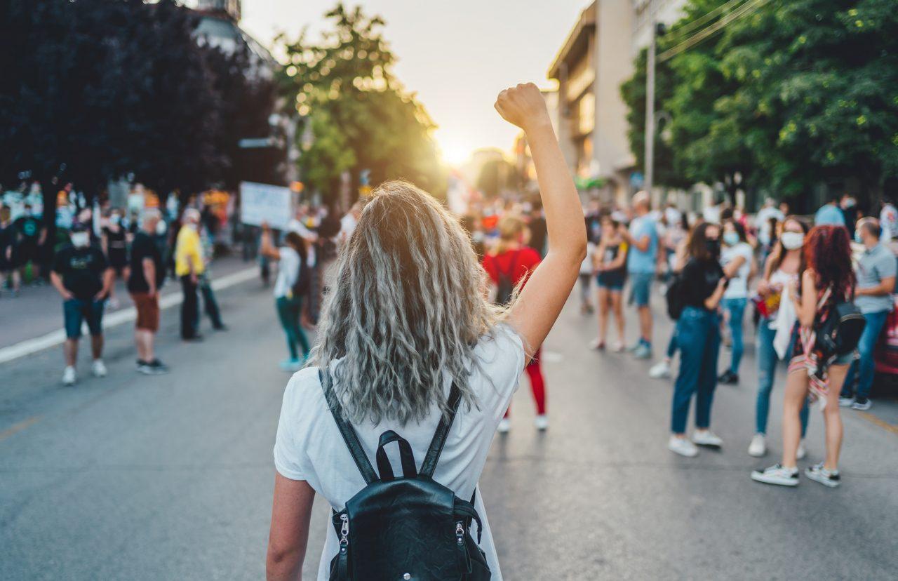 Ung kvinne med hevet knyttneve i gatene under en streik, eller protest.