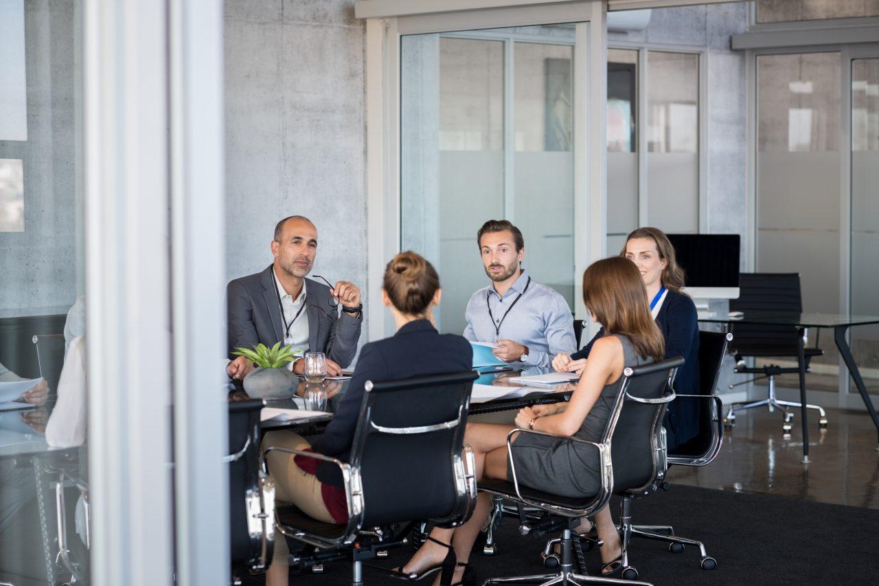 Flere mennesker rundt et bord på et møterom.
