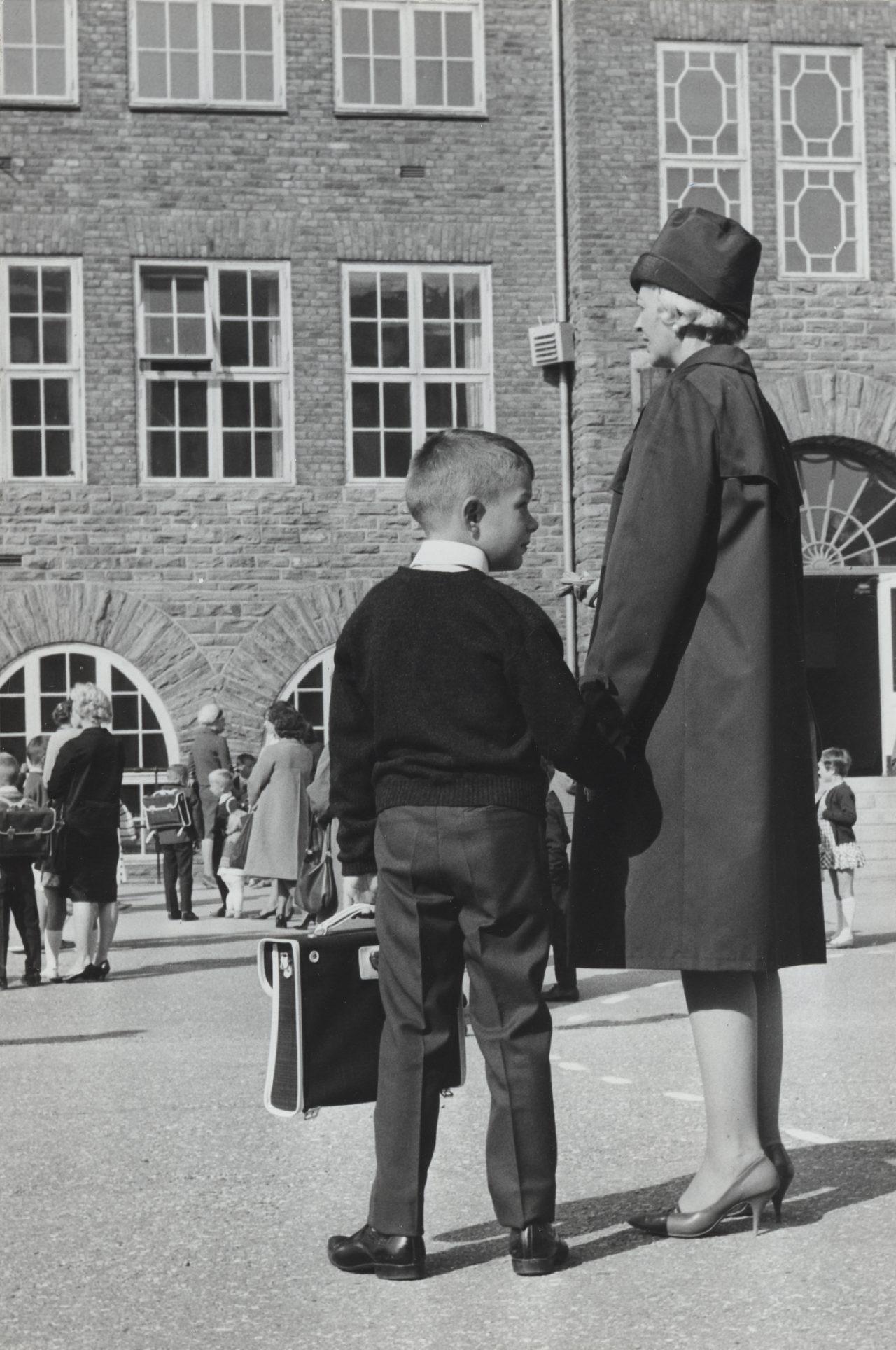 Svart hvitt bilde. Pent kledd ung gutt holder mors hånd i skolegården på første skoledag. I andre hånden har han en skoleveske.