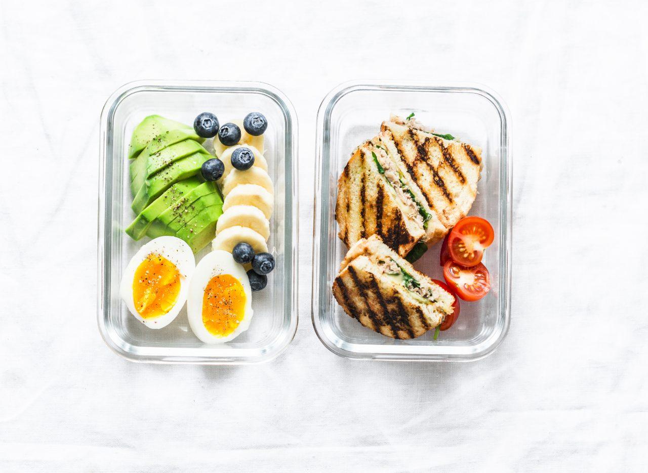 To matbokser i glass på marmormønstret benkeplate. Ene boksen har toast og tomater, den andre avokado, kokt egg, blåbær og banan.