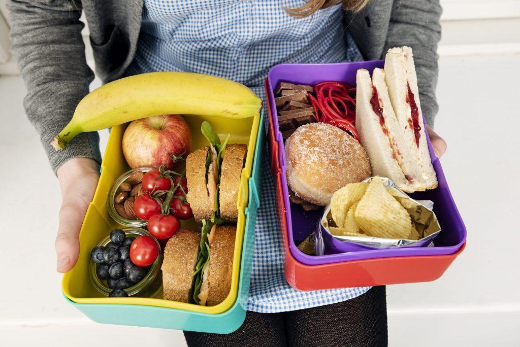 Tett på fanget til en jente i kjole. HUn holder to matpakker i hendene. Ene matpakka inneholder brødskiver, frukt og bær, mens den andre inneholder loff med syltetøy, potetgull og sjokolade.